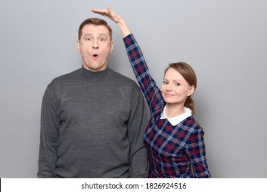 Studio shot of short woman standing and showing height of tall man, woman is smiling, man is amazed, over gray background. Concept of diversity of people's heights, tall and short persons - Shutterstock ID 1826924516