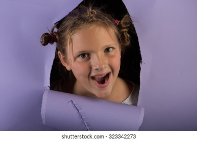 Studio shot of a silly girl with glitter in her hair breaking through purple paper with a crazy look and silly hair.
