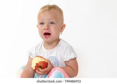 Studio shot of sitting cool toddler girl holding red apple and looking on the side of the camera with an open mouth.