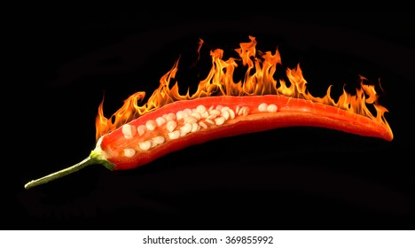studio shot of a sliced burning red chili in dark back
