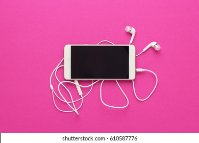 studio shot of smartphone and earbuds on magenta background