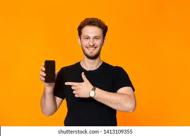Studio shot of a smiling bearded young man with headset pointing a finger at the smartphone while standing over orange background. Positive thinking