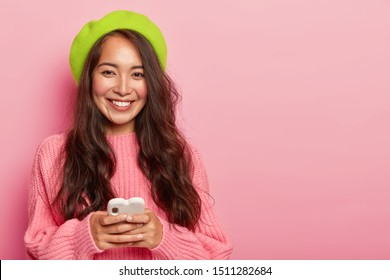 Studio shot of smiling brunette woman with long hair, wears bright green beret and oversized jumper, holds modern cell phone, connected to wireless internet, has pleased expression. Online chatting