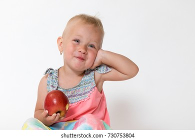 Studio shot of smiling toddler girl sitting and holding red apple. The girl touches her face by hand.