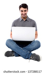 Studio shot of a smiling young guy sitting on the floor with laptop.