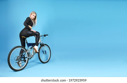 studio shot of a sportive woman sitting on a bicycle on blue background with copy space. beautiful young woman wearing sportswear posing with a bike in a photo studio - Shutterstock ID 1972923959