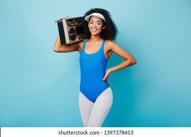 b7f06f2e4d8 Studio shot of sporty african woman with boombox. Smiling black girl  enjoying aerobics with music