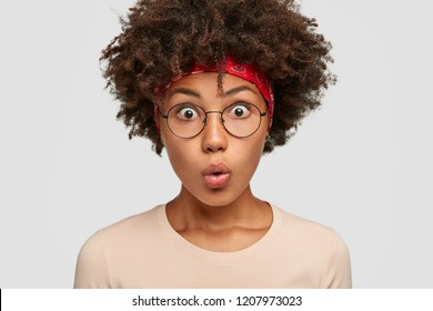 Studio shot of startled young woman with bated breath, opened eyes, looks with wonderment at camera, reacts on sudden news, wears red headband, isolated over white background. People and shock