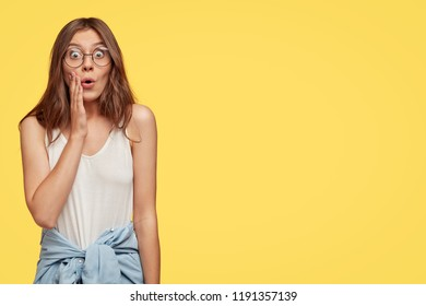 Studio shot of stupefied emotional European woman expresses wonder, hears news or rumours from interlocutor, wears transparent glasses, poses over yellow background, copy space for your text
