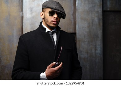 Studio shot of stylish african american man wearing coat, cap, glasses and holding smoking pipe