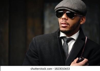 Studioaufnahme eines stilvollen afrikanischen Amerikaners mit Mantel, Kappe, Brille und Rauchrohr