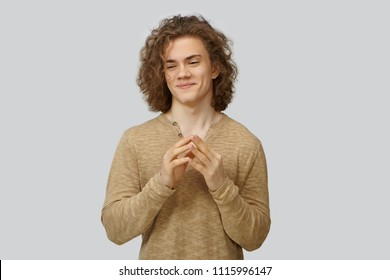 Studio shot of stylish sly young European man with voluminous curly hairstyle smiling mysteriously and clasping hands, scheming, planning tricky joke, going to prunk his best friend. Human emotions