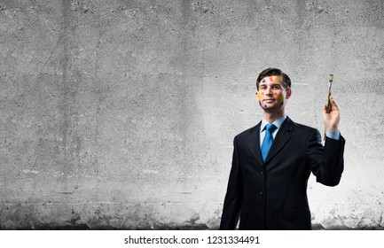 Studio shot of successful and confident keeping paintbrush in his hand and looking away while standing against dark gray wall on background