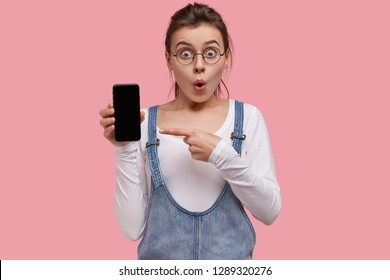 Studio shot of surprised European young woman points at blank screen, holds cell phone, amazed with its functions, wears transparent glasses, poses against pink background, advertises technology