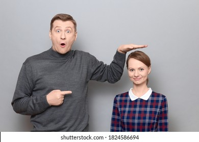 Studio shot of surprised tall man showing height of short woman, pointing at her with finger, both are standing over gray background. Concept of diversity of people's heights, tall and short persons