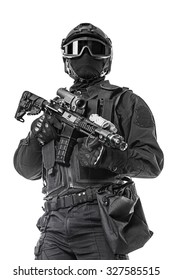 Studio shot of swat operator with assault rifle. Tactical helmet gloves, eyewear. Security forces concept. Low angle view