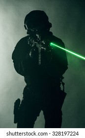 Studio shot of swat police operator with laser sights on rifle. Fire smoke screen green background. Laser rays beams diagonal