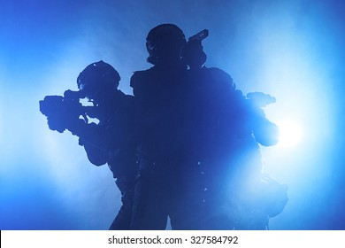 Studio shot of swat police special forces black uniforms aiming terrorists automatic rifle. Tactical helmet vest goggles. Blue smoke background