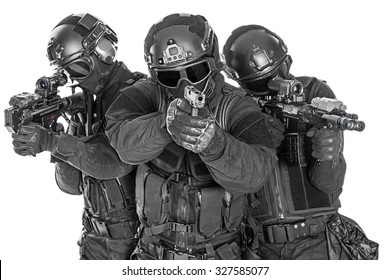 Studio shot of swat police special forces black uniforms pointing terrorists automatic rifle. Tactical helmet goggles. Isolated on white front view