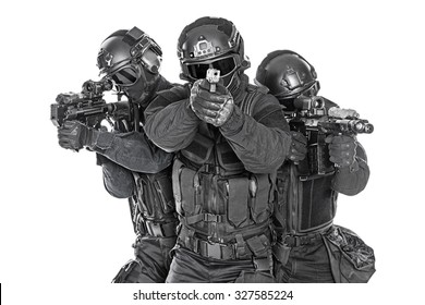 Studio shot of swat police special forces black uniforms pointing terrorists pistol automatic rifle. Tactical helmet vest goggles. Isolated on white