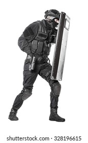 Studio shot of swat police special forces with pistol hiding behind ballistic shield moving treading. Isolated on white full body portrait