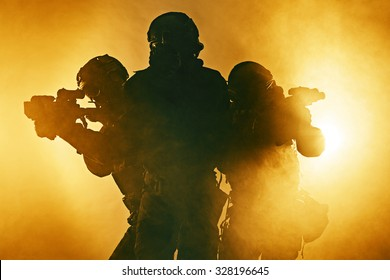 Studio shot of swat police special forces black uniforms aiming terrorists automatic rifle. Tactical helmet vest goggles. Fire smoke background