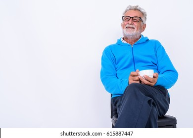 Studio shot of thoughtful happy senior bearded man smiling while holding coffee cup and sitting on chair ready for gym against white background