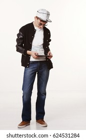 Studio shot of trendy teen in a cap and sunglasses and holding a tablet isolated on white background