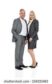 Studio shot of two business colleagues standing together looking at camera smiling over white background