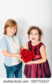 Studio shot of two funny kids friends holding big red heart
