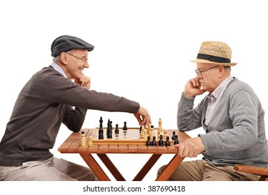 Studio shot of two old friends playing a game of chess at a wooden table isolated on white background