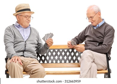 Studio shot of two older men playing cards seated on a wooden bench isolated on white background