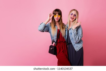Studio shot of two  pretty girls in  similar jeans jacket posing on pink background . Best friends  having fun together .