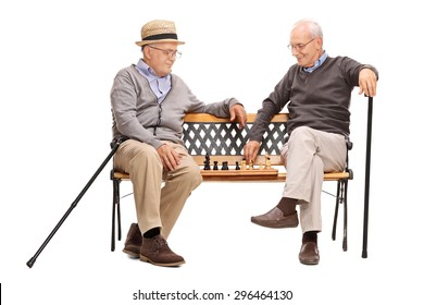 Studio shot of two seniors playing a game of chess seated on a wooden bench isolated on white background