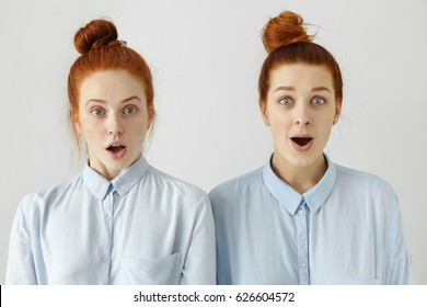 Studio shot of two sisters or friends looking alike with their identical blue shirts and same hairstyles looking at camera in full disbelief, shocked or surprised with some news, gossips or rumours