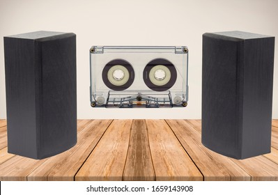 A studio shot of two stereo black speakers with a Cassette tape k7 isolated on a empty room with wooden floor and beige wall at the background.