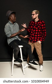 Studio shot of two stylish young men having fun. Handsome bearded hipster in a shirt in a cage standing next to his African-American friend in hat against a dark background.