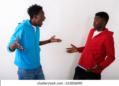 Studio shot of two young black African friends looking confused together against white background