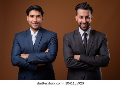 Studio shot of two young Iranian businessmen together against brown background