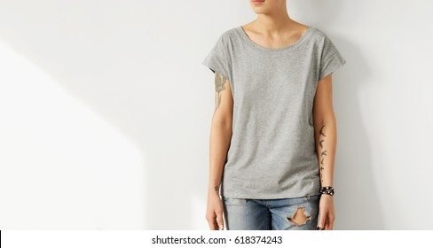 Studio shot of unrecogizable young European female hipster with perfect slim body dressed in oversize grey t-shirt posing indoors at blank wall with copy space for your text or advertising content