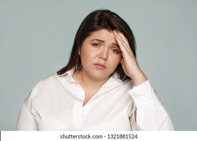Studio shot of upset frustrated young chubby female employee wearing formal shirt holding hand on her forehead, having mournful look, suffering from headache or hangover after sleepless night