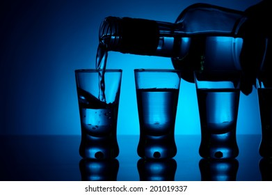 Studio shot Vodka poured into a glass with glasses lit with blue backlight