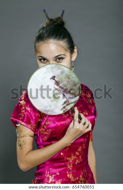 Studio shot of a woman in her early twenties, wearing traditional chinese clothing shy attitude.