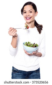 Studio shot of a woman holding delicious green salad