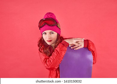 Studio shot woman in rad wearing ski clothes standing in red background with purple snowboard and ski mask