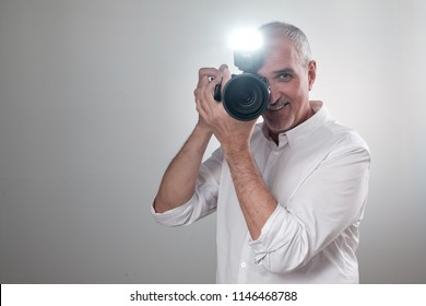 Studio shot of ymature spanish man with camera against grey background. Experienced photographer in photo studio