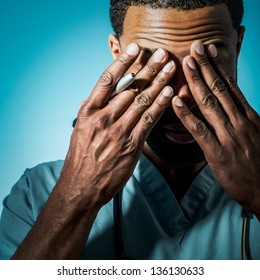 Studio shot of a young African American doctor suffering fatigue and rubbing his eyes.