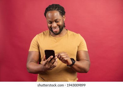 Studio shot of young African American man standing isolated on red wall holding mobile phone and typing message, chatting with friend on social media online, using dating app, enjoying new application