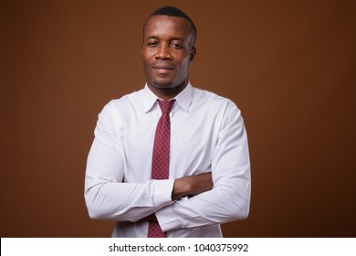 Studio shot of young African businessman wearing white shirt and tie against brown background