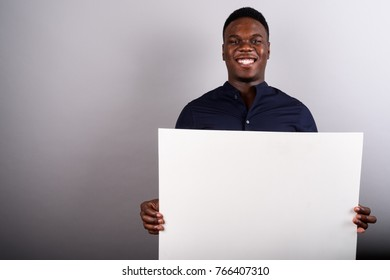 Studio shot of young African businessman against white background
